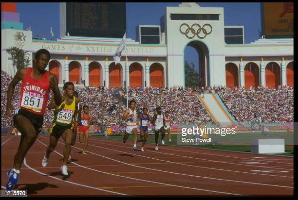 ATHLETES POWER THEIR WAY OFF THE BACK STRAIGHT DURING A HEAT FOR THE MENS 400 METRE AT THE 1984 LOS ANGELES OLYMPICS