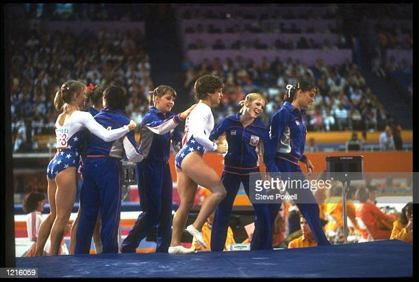 MARY LOU RETTON OF THE UNITED STATES IS CONGRATULATED BY TEAM MATES AFTER SCORING A PERFECT 100 DURING THE VAULT SECTION OF THE TEAM COMBINED...