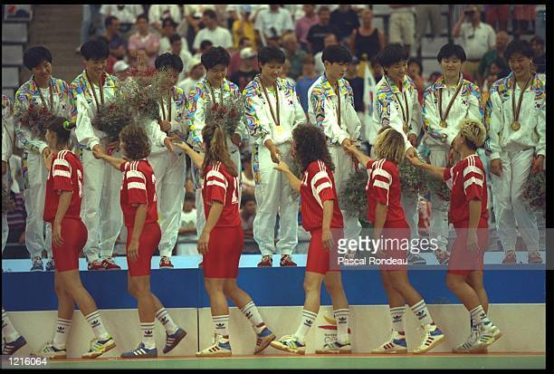 THE WOMENS HANDBALL TEAM FROM NORWAY SHAKE HANDS WITH THE TEAM FROM KOREA AS THEY MOVE ON TO COLLECT THEIR SILVER MEDALS AT THE 1992 BARCELONA...