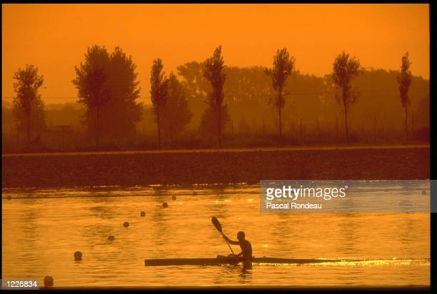 A CANOEIST PRACTICES ON THE OLYMPIC COURSE AT SUNSET DURING THE 1992 BARCELONA OLYMPICS