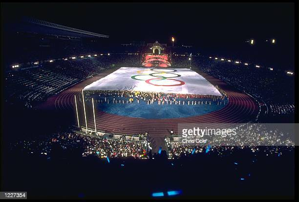 A GIANT OLYMPIC FLAG IS PULLED ACROSS THE FIELD INSIDE THE OLYMPIC STADIUM DURING THE OPENING CEREMONY OF THE 1992 BARCELONA OLYMPICS