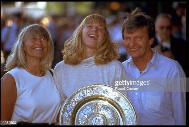 STEFFI GRAF OF GERMANY FLANKED BY HER PARENTS HEIDI AND PETER HOLDS THE TROPHY AFTER WINNING THE 1991 WIMBLEDON TENNIS CHAMPIONSHIPS GRAF DEFEATED...