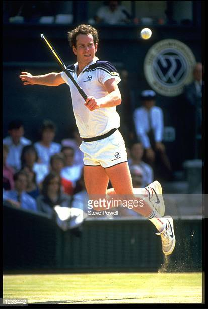 JOHN MCENROE OF THE UNITED STATES LEAPS INTO THE AIR TO MAKE A SHOT DURING A MATCH AT THE 1984 WIMBLEDON TENNIS CHAMPIONSHIPS