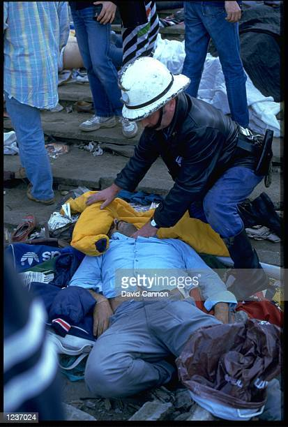 A RESCUER CHECKS FOR SIGNS OF LIFE FROM AN INJURED SUPPORTER WHO WAS CAUGHT UP IN A RIOT PRIOR TO THE EUROPEAN CUP FINAL IN THE HEYSEL STADIUM IN...