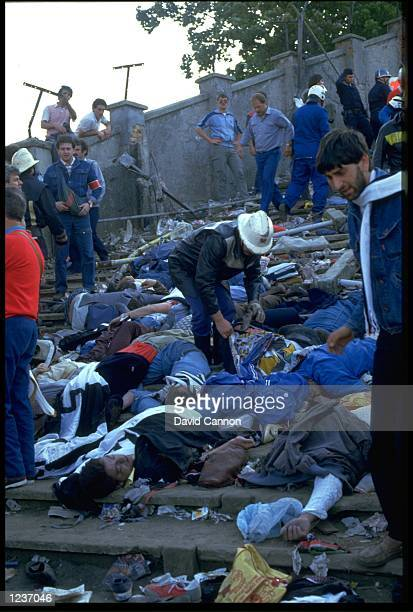 RESCUERS CHECK FOR SIGNS OF LIFE AMONGST THE BODIES LYING ON THE TERRACES OF THE HEYSEL STADIUM AFTER A WALL COLLAPSED KILLING 39 SUPPORTERS DURING A...
