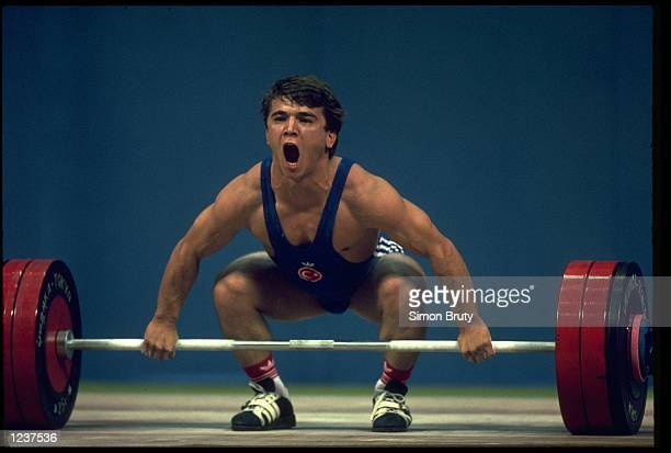 NAIM SULEYMANOGLU OF TURKEY STRUGGLES TO LIFT THE 1525 KG WEIGHTS DURING THE FEATHERWEIGHT 60KG SNATCH COMPETITION AT THE 1988 SEOUL SUMMER OLYMPICS...
