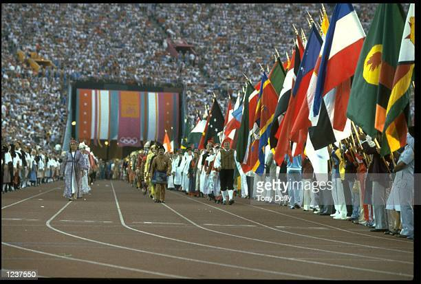 REPRESENTATIVES FROM THE OLYMPIC NATIONS MARCH PAST THE NATIONAL FLAGS DURING THE OPENING CEREMONY OF THE 1984 LOS ANGELES OLYMPICS
