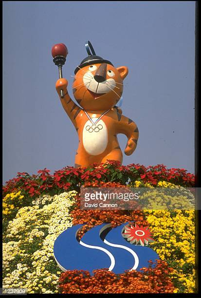 HODORI THE OLYMPIC MASCOT HOLDS THE OLYMPIC TORCH ABOVE HIS HEAD WHILST STANDING ON TOP OF A MOUNTAIN OF FLOWERS DURING THE 1988 SEOUL OLYMPICS