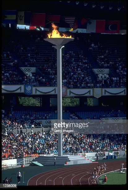 THE OLYMPIC FLAME IN ALL ITS GLORY AS ATHLETES RUN DOWN THE STRAIGHT AT THE 1988 SUMMER OLYMPICS IN SEOUL IN SOUTH KOREA