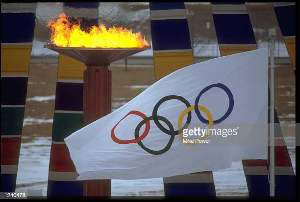 THE OLYMPIC FLAME AND FLAG CAN BE SEEN DURING THE OPENING CEREMONY OF THE 1988 WINTER OLYMPICS HELD IN CALGARY IN CANADA