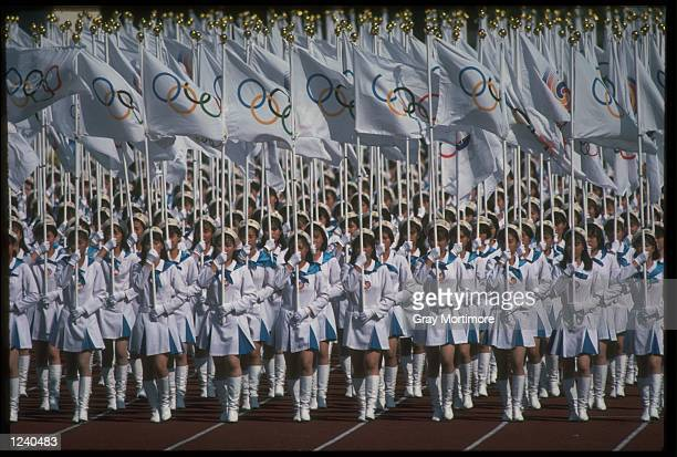 A LARGE GROUP OF WOMEN MARCH THROUGH THE OLYMPIC STADIUM CARRYING SMALL OLYMPIC FLAGS DURING THE OPENING CEREMONY OF THE 1988 SUMMER OLYMPICS HELD IN...