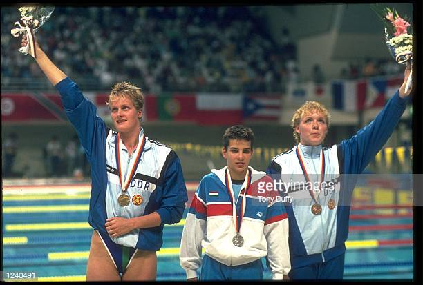 KRISTIN OTTO OF EAST GERMANY CELEBRATES RECEIVING HER GOLD MEDAL ALONG WITH KISZTINA EGERSZEGI OF HUNGARY AND CORNELIA SIRCH OF EAST GERMANY AFTER...