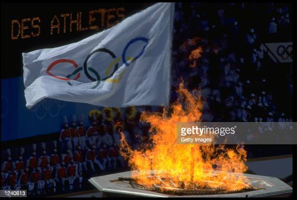 THE OLYMPIC FLAG BLOWS IN THE WIND AS THE OLYMPIC FLAME BURNS BRIGHTLY IN THE FOREGROUND DURING THE OPENING CEREMONY OF THE 1988 SUMMER OLYMPICS HELD...