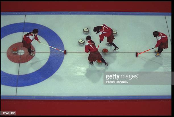 TEAM MEMBERS FROM JAPAN CLEAR A PATH FOR THE CURLING STONE DURING THEIR CURLING MATCH AGAINST GREAT BRITAIN AT THE 1992 WINTER OLYMPICS IN...
