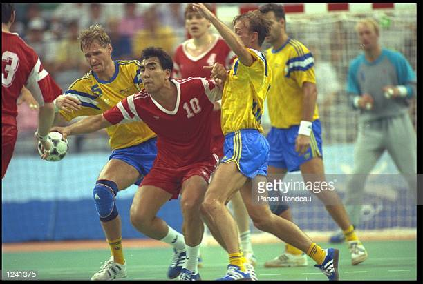 DOUICHEBAEV OF THE EUN FIGHTS OFF A CHALLENGE FROM TWO SWEDESH PLAYERS DURING THE FINAL OF THE MENS TEAM HANDBALL COMPETITION AT THE 1992 BARCELONA...