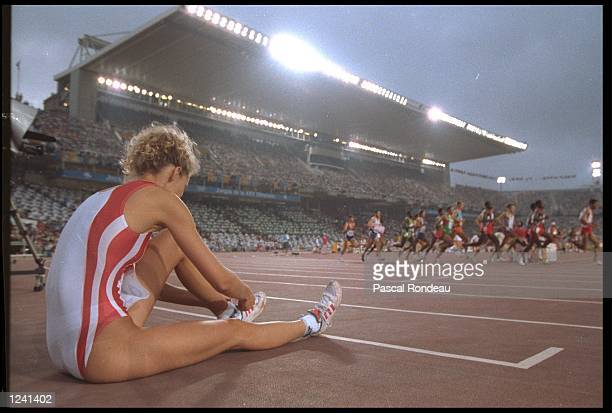 HEIKE HENKEL OF GERMANY WATCHES THE MENS 5000 METRE FINAL AS SHE PREPARES TO ATTEMPT A JUMP DURING THE WOMENS HIGH JUMP COMPETITION AT THE 1992...