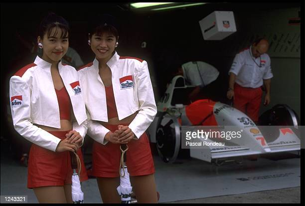 TWO JAPANESE MODELS REPRESENTING MARLBORO STANDING OUTSIDE THE MCLAREN PEUGEOT PIT GARAGE BEFORE THE JAPANESE GRAND PRIX SUZUKA DAMON HILL OF GREAT...