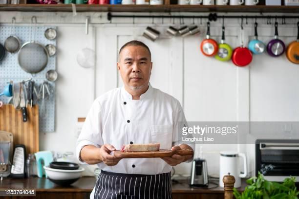 一個亞洲中年廚師在廚房 - 郷土料理 ストックフォトと画像