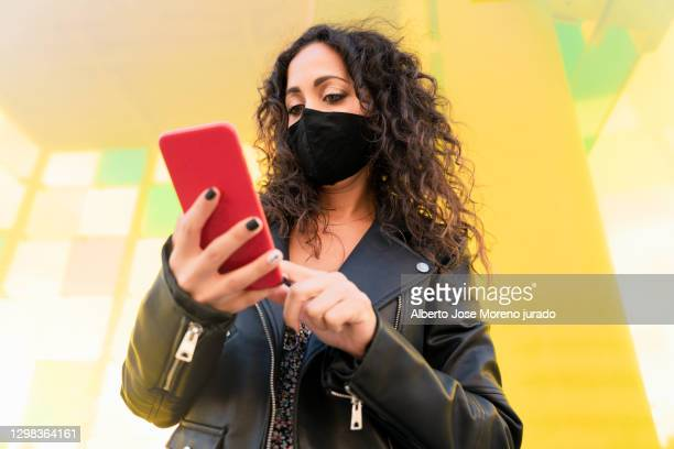 beautiful girl with curly black hair using mobile phone - black nail polish stock pictures, royalty-free photos & images