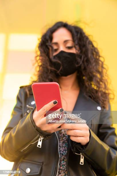 young brunette girl with curly hair using mobile phone - black nail polish stock pictures, royalty-free photos & images