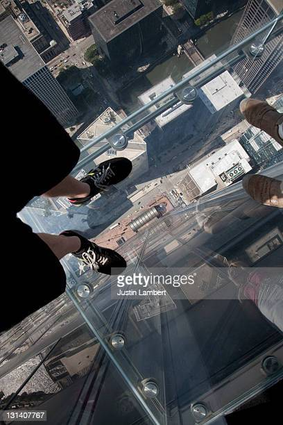 LOOKING AT FEET THROUGH GLASS AT WILLIS TOWER