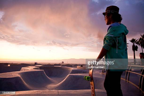 MAN STANDS LOOKING AT SKATE PARK IN SUNSET L.A