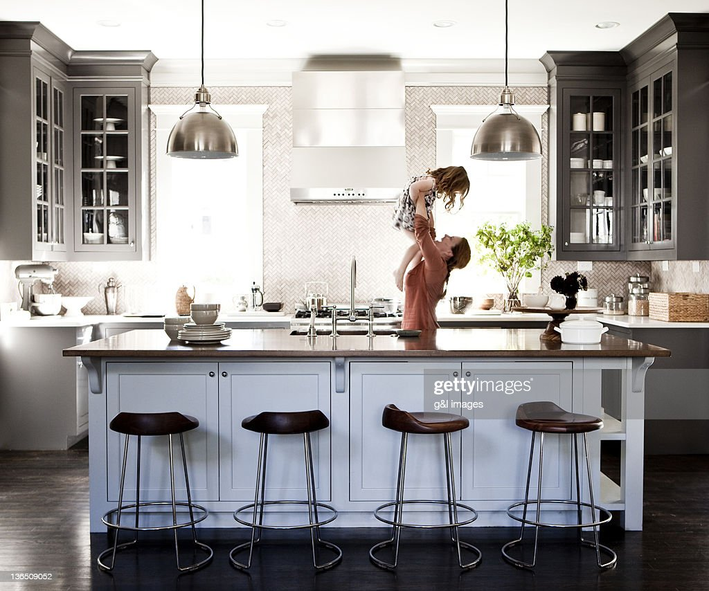 MOTHER LIFTING DAUGHTER IN KITCHEN : Stock Photo