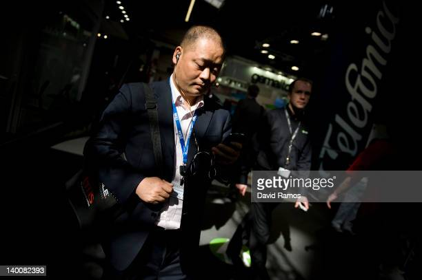 A visitor checks his mobile phone as he attends the first day of the Mobile World Congress on February 27 2012 in Barcelona Spain The annual Mobile...