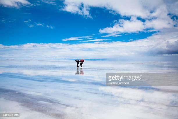 COUPLE WITH UMBRELLA WALK IN SALT FLATS IN BOLIVIA