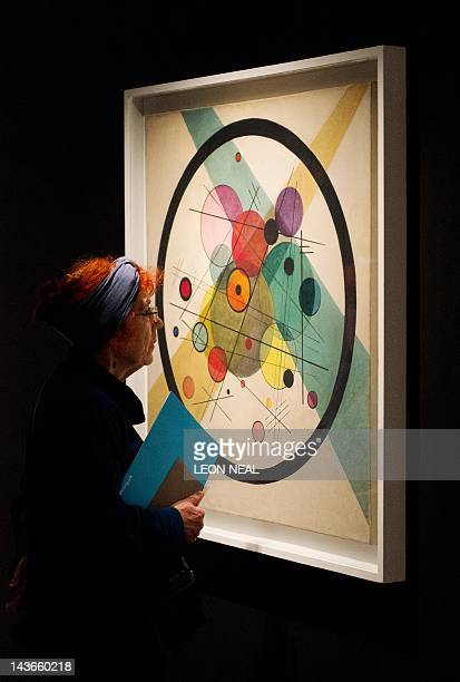 A woman studies 'Circles in a Circle' by Russian painter Wassily Kandinsky in the Barbican centre in central London on May 2 2012 as the venue...