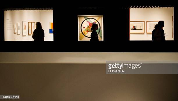 A woman passes Circles in a Circle by Russian painter Wassily Kandinsky on the wall of the Barbican centre in central London on May 2 2012 as the...