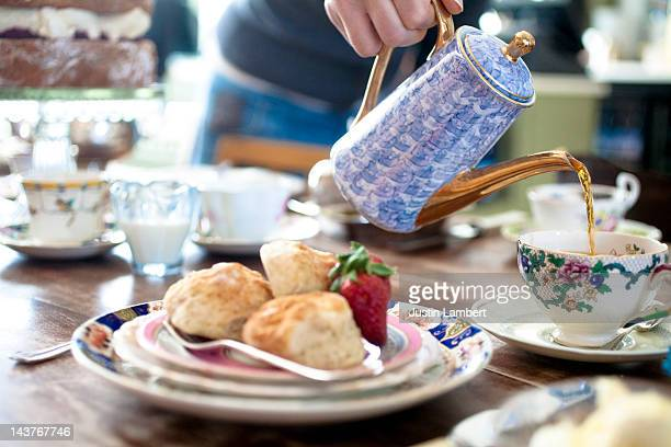 lady pouring tea for english cream tea - english teapot stock pictures, royalty-free photos & images