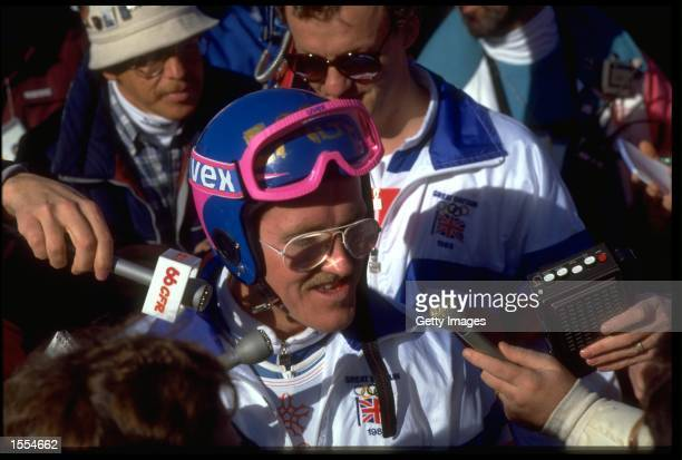 MICHAEL '' EDDIE THE EAGLE '' EDWARDS OF GREAT BRTIAIN IS MOBBED BY REPORTERS DURING THE 90 METRE SKI JUMP COMPETITION AT THE 1988 WINTER OLYMPICS...