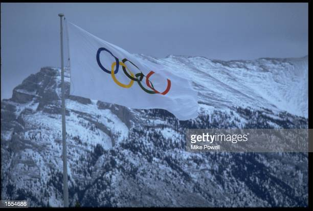 THE OLYMPIC FLAG BLOWS IN THE STRONG WINDS OF CANADA IN FRONT OF AN IMPRESSIVE BACKDROP OF SNOWY MOUNTAIN TOPS DURING THE 1988 WINTER OLYMPICS HELD...