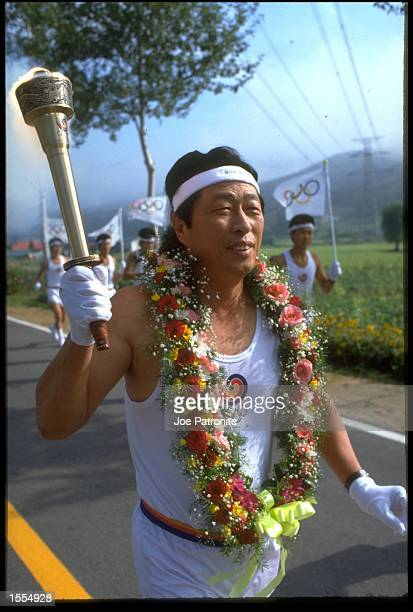 ONE OF THE OLYMPIC TORCH BEARERS MAKES HIS WAY TO THE OLYMPIC STADIUM IN SEOUL IN PREPERATION FOR THE OPENING CEREMONY OF THE 1988 SUMMER OLYMPICS IN...