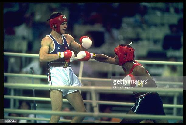 ROY JONES OF THE UNITED STATES THROWS A RIGHT HOOK AT RICHARD WOODHALL OF GREAT BRITAIN DURING THE SEMI FINALS OF THE JUNIOR MIDDLEWEIGHT BOXING...