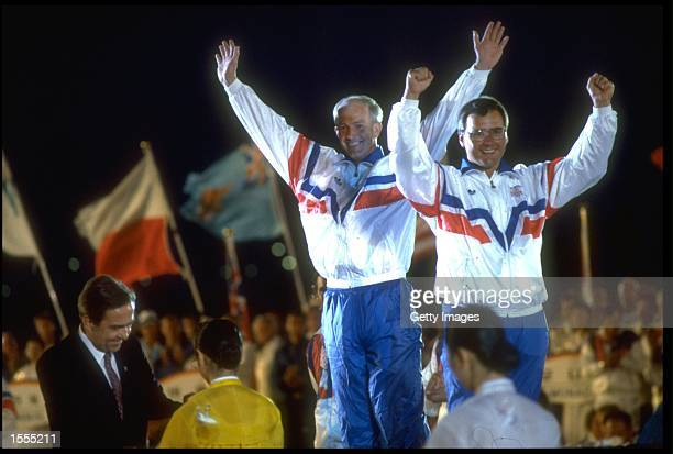 MICHAEL MCINTYRE AND BRYN VAILE OF GREAT BRITAIN RAISE THEIR ARMS TO CELEBRATE AS THEY RECEIVE THEIR GOLD MEDALS FOR WINNING THE STAR CLASS YACHTING...