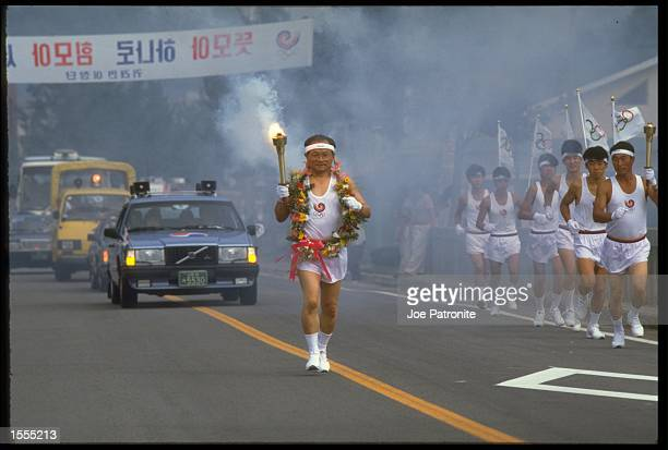 AN ATHLETE FROM KOREA CARRIES THE OLYMPIC TORCH ON ITS LONG JOURNEY AS HE MAKES HIS WAY TOWARDS THE OLYMPIC STADIUM IN SEOUL FOR THE OPENING CEREMONY...