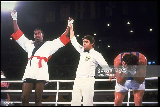 HENRY TILLMAN OF THE UNITED STATES HAS HIS ARM RAISED BY THE REFEREE AFTER DEFEATING ANGELO MUSONE OF ITALY IN THEIR SEMI FINAL HEAVYWEIGHT BOXING...