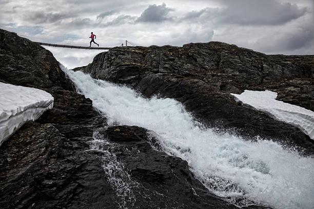 RUNNING ACROSS A BRIDGE ABOVE A WATERFALL Wall Art