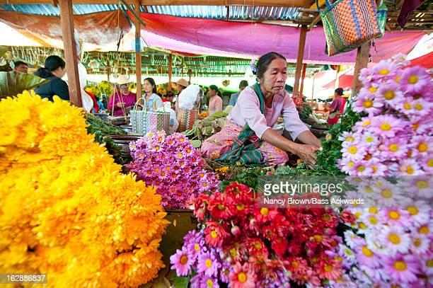 WOMAN SELLING FLOWERS IN MARKET IN MYANMAR.