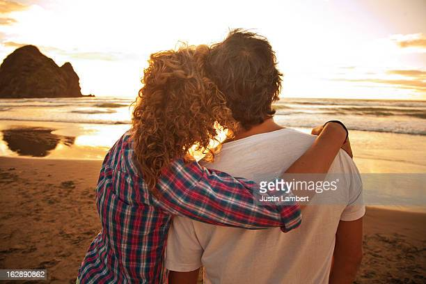 COUPLE WATCHES THE SUN SETTING AT THE BEACH