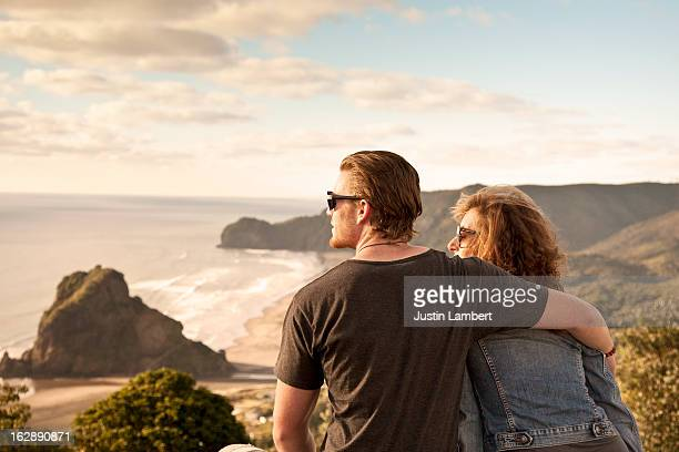 couple looks at view of piha beach new zealand - auckland - fotografias e filmes do acervo