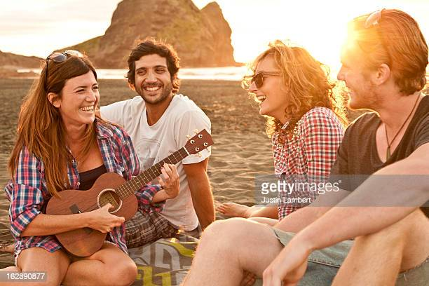 GROUP OF FRIENDS ENJOYING THE SUNSET AT THE BEACH