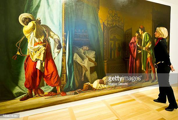 A member of staff stands in front of Where Should Othello Go the painting by Pompeo Molmenti restored thanks to backing by Louis Vuitton as part of a...