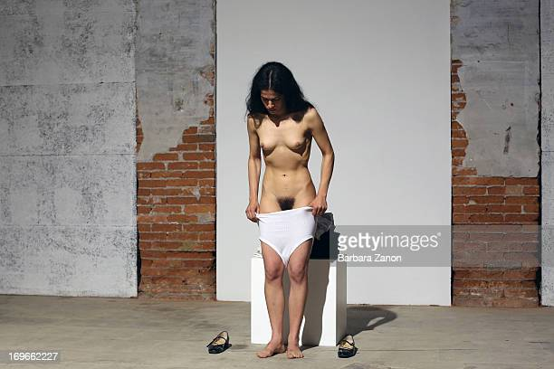 A woman stands partially naked as she pulls up her pants during a performance inside Italia Pavilion during the official opening of the 55th...