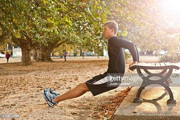 MAN EXERCISING IN PARK PERFORMING 'DIPS'