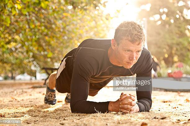 MAN EXERCISING IN PARK PERFORMING A PLANK