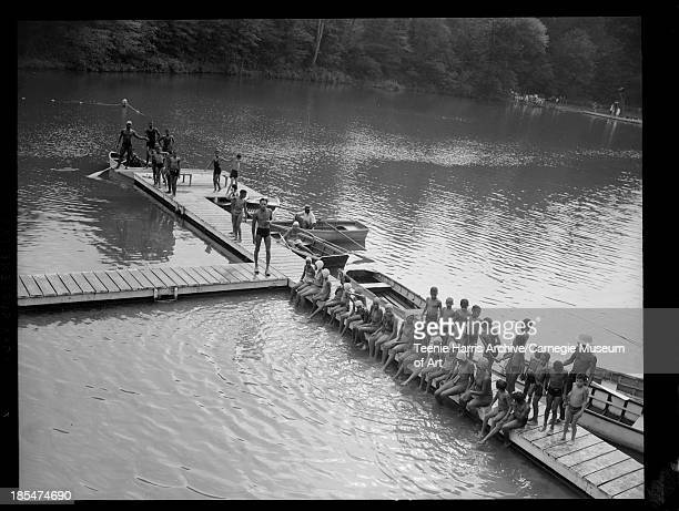 Group of boys and girls gathered on dock with two young men and a young women seated in rowboats at Camp Weldon Johnson Beaver County Pennsylvania...