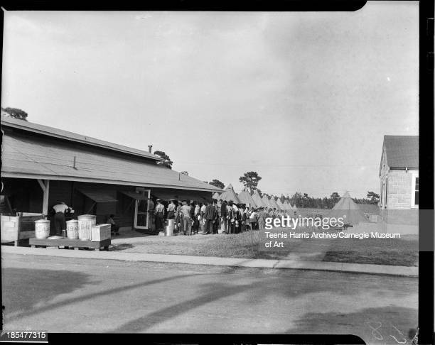 Soldiers holding pans lined up outside one story clapboard mess hall with circular tents in background Fort Bragg North Carolina August September 1940